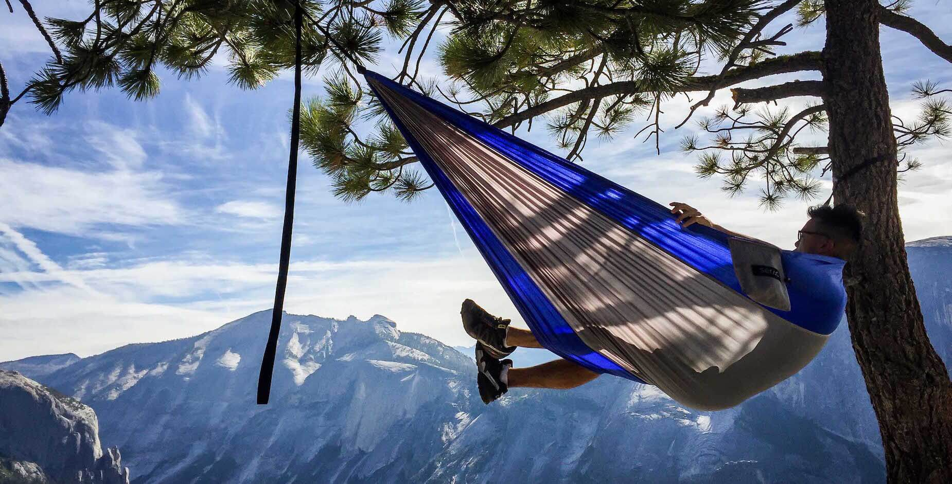 sitting in a portable serac camping hammock in yosemite. Classic model with iceberg colors