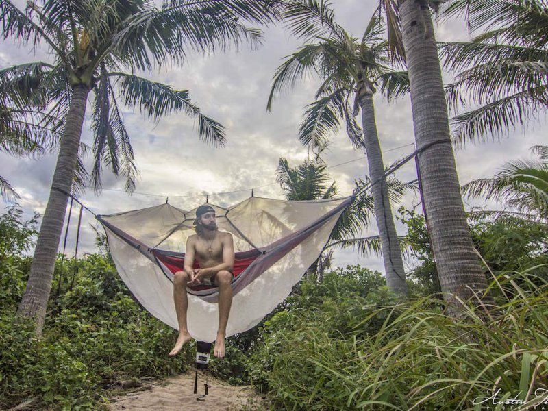 austin hammocking in a serac double hammock with mosquito bug net among palm trees